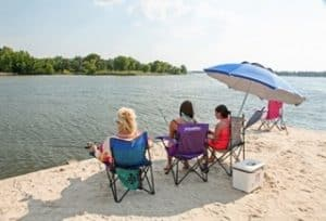 3 people sitting in chairs fishing on the bank of a lake
