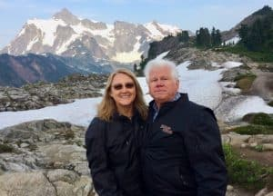 A Couple standing in front of a snow and mountains background